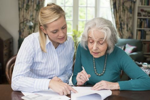 Woman Helping Senior woman With Paperwork