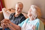 Smiling senior couple talking on sofa while holding walking cane.